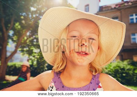 Summer day in the city. Little girl with a dirty mouth after eating ice cream.