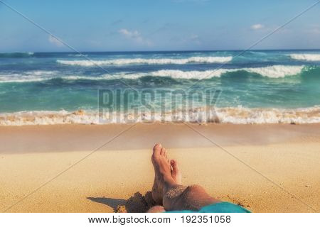 Man enjoying at the beach - focus is on feet.