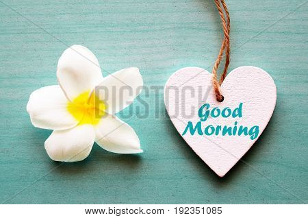 Good Morning.Decorative white wooden heart with frangipani flower and text