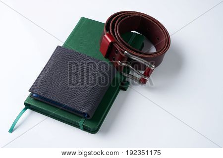 Stylish men accessories. Notebook brown leather belt and a black wallet on a white background.