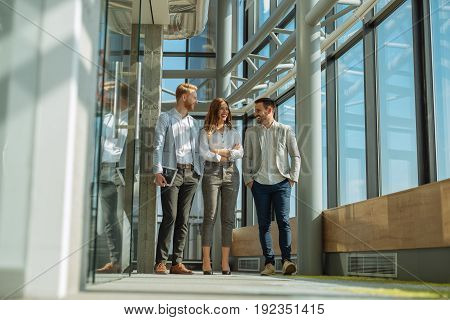 Portrait of three businesspeople walking and talking about the project they work on together. Businessman is holding a digital tablet they are all smart dressed.