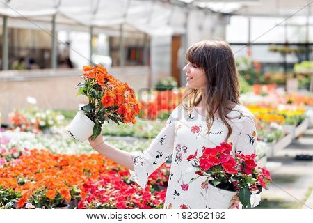 Young woman buying flowers at a garden center. selects bright colorful potted plants flowers. Flowers in pot in fertilized soil