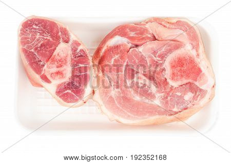 Pork knuckle in a plastic container isolated on white background. Top view.