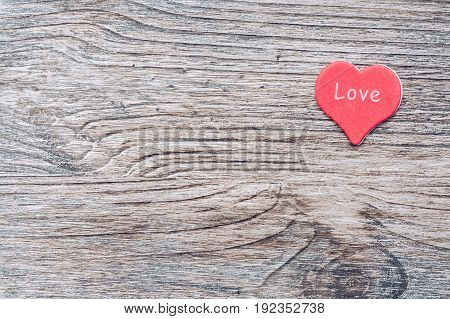 red heart on a wooden surface. The wooden background with heart.