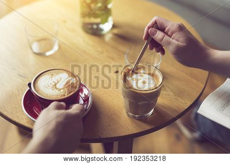 Top view of two people holding a nicely decorated latte art coffee cups enjoying their morning coffee. Selective focus