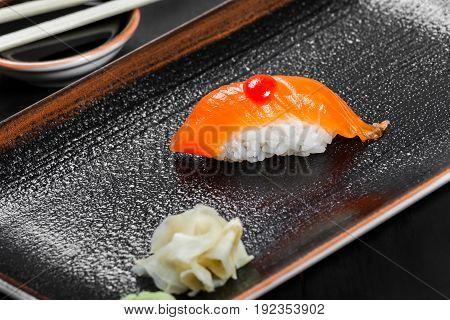 Nigiri with salmon on dark wooden background. Gunkan Sushi set. Japanese cuisine. Top view