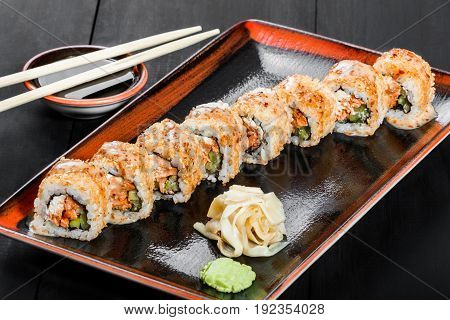 Sushi Roll - Maki Sushi made of salmon cucumber avocado and cream cheese on dark wooden background. Top view. Japanese cuisine
