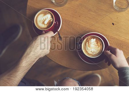 Top view of two people holding a nicely decorated latte art coffee cups enjoying their morning coffee. Focus on the coffee on the right