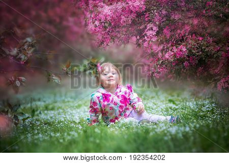 Little happy girl  under blooming crabapple tree with pink flowers