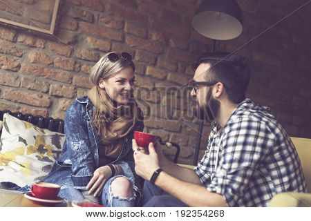 Young couple in love sitting in a cafe drinking morning coffee and having a pleasant conversation. Focus on the girl