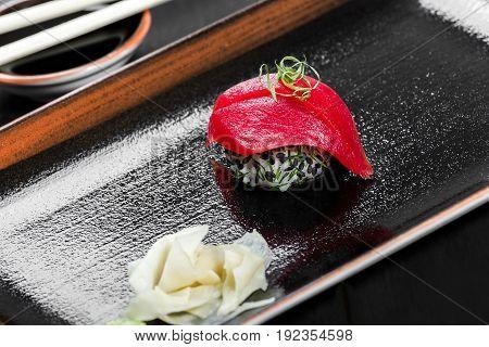 Nigiri with tuna on dark wooden background. Gunkan Sushi set. Japanese cuisine. Top view