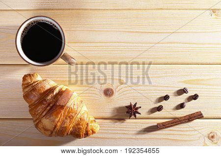 Cup of hot coffee and fresh croissant on wooden table top view. Low illumination. Space for text