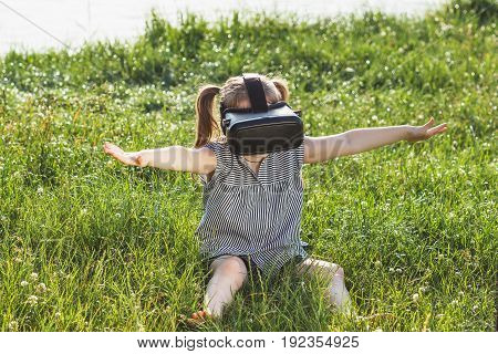 Little Girl Plays Game With Virtual Reality Glasses Outdoors
