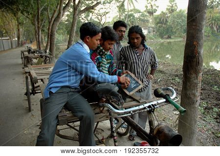 KOLKATA, JANUARY 20, 2007: A young boy is teaching a group of cycle van driver to understand the alphabets on January 20, 2007 in a rural area near Kolkata, India.