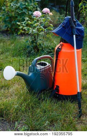 Fertilizer pesticide garden sprayer and watering can on lawn with green grass