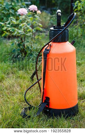 Fertilizer pesticide garden sprayer on lawn with green grass
