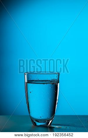 Photo of glass with water on empty blue background
