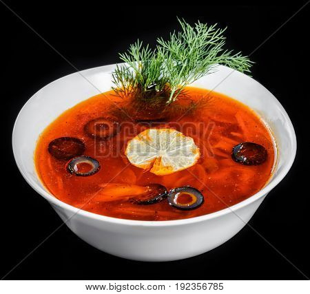 Soup with meat olives herbs and lemon in bowl isolated on black background homemade food. Traditional Russian soup - solyanka