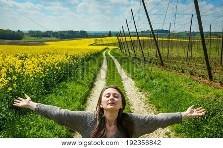 A woman spreading her arms standing on a pathway leading through the yellow flowering rapeseed and hop fields in spring.