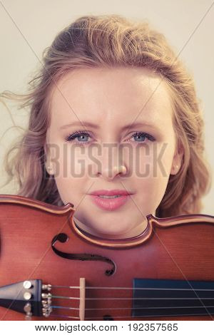 Classical music passion concept. Musician violinist woman holding her violin enjoying hobby.