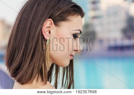 Portrait of young female with short brown hair and evening make up with fake eyelashes. Bob cut hairstyle