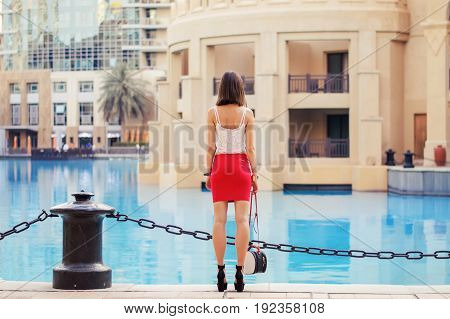 Skinny and tall european woman in white crop top and short red skirt with small bag and high heel shoes standing near waterfront in Dubai downtown