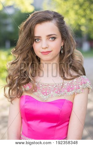 Vertical portrait of teenage girl with long curly hair trendy and accurate make up and in cocktail dress of pink color