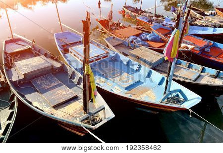 Row of small wooden fishing boats at the fishery harbor photo with sunset low and soft lighting.
