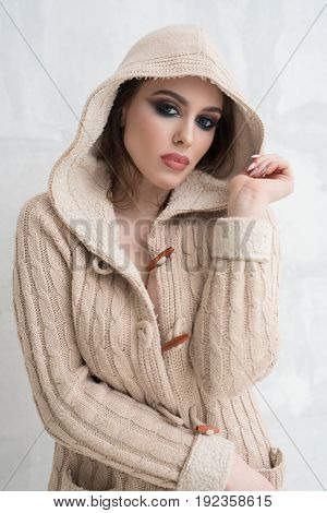 Sexy girl with bright makeup posing in a cosy cardigan with a hood put on studio shot