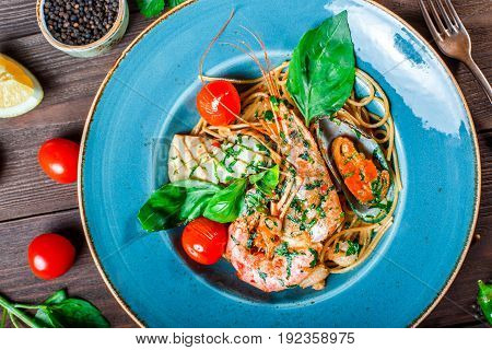 Italian pasta spaghetti with seafood langoustine mussels squid scallops shrimp Parmesan cheese fresh basil and tomatoes on rustic wooden background. Mediterranean food. Top view