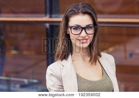 Portrait of a smiling female with short hair eye glasses beige jacket. Happy business woman