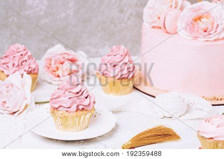 Pink cupcakes with roses and holiday cake. Festive and bright. Wedding Celebration concept