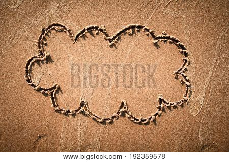 A speech cloud or think bubble drawn out on a sandy beach. Beach background. Top view