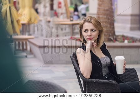 Horizontal photo of young european female sitting at the open air terrace with a paper cup of coffee. Lifestyle concept. Coffee break