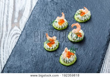 Appetizer canape with red caviar shrimp and cream cheese on stone slate background close up. Delicious snacks sandwiches crostini bruschetta antipasti on party or picnic time. Top view