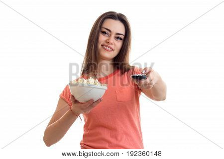 Cutie brunette girl watch a tv with pop-corn and smiles isolated on white background