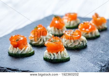 Appetizer canape with salmon cucumber and cream cheese on stone slate background close up. Delicious snacks sandwiches crostini bruschetta antipasti on party or picnic time. Top view