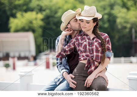 young cowboy kissing his sensual girlfriend while sitting on fence at ranch