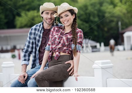 young cowboy style couple embracing and looking at camera while sitting on fence