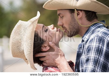young sensual cowboy style couple kissing with eyes closed outdoors