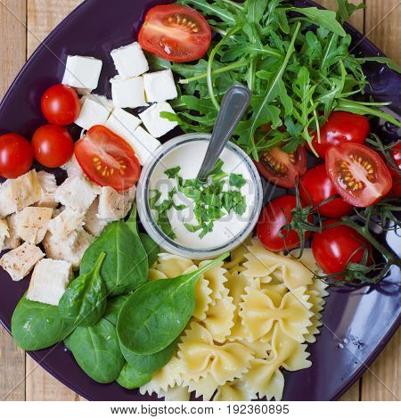 Square photo of pasta salad: farfalle spinach leaves arugula red cherry tomatoes feta cheese chicken breast and white sauce in a small bowl. Top view