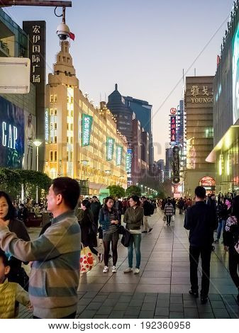 Shanghai, China - Nov 4, 2016: Night scene along Nanjing Road Pedestrian Street - Buildings with colorful lights in western architectural designs. People walking on the street.