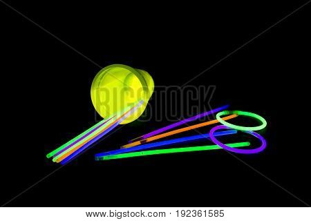 Yellow fluorescent glass fallen with glow sticks neon light on back background. variation of different colored chem lights