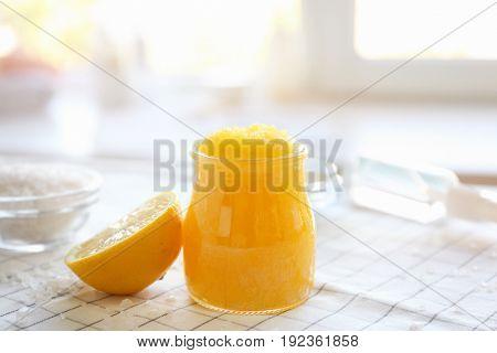 Glass jar with natural body scrub and lemon slice on napkin