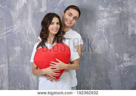 Beautiful young couple with pillow in heart shape on grunge wall background