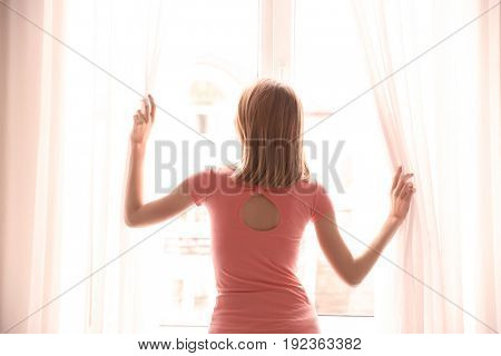 Young woman opening curtains