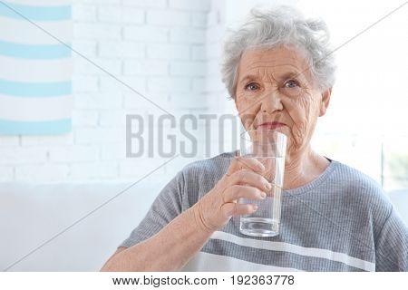 Elderly woman holding glass of water at home. Concept of retirement
