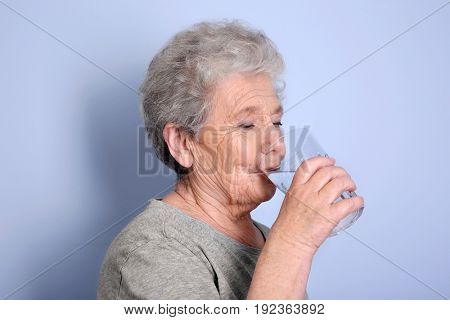 Elderly woman drinking water on grey background. Concept of retirement