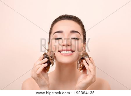 Beautiful young woman with giant Achatina snails on color background