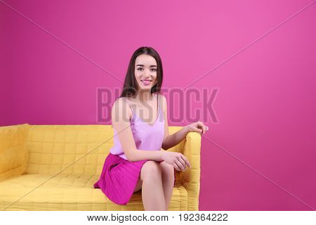 Beautiful young woman in lilac top and bright skirt sitting on sofa against color background